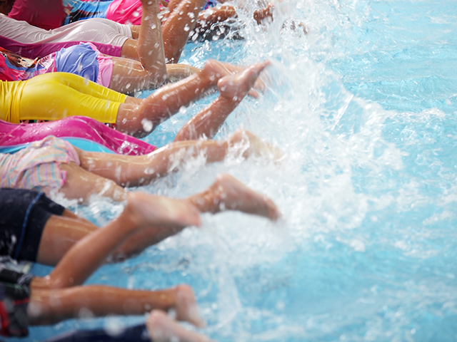 group of children at swimming pool class learning to swim